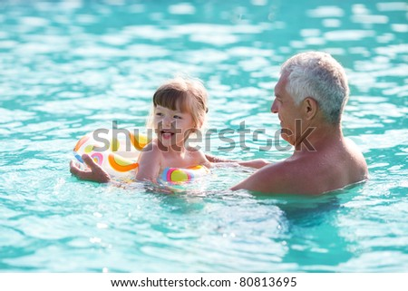 grandfather and granddaughter swimming in the pool - stock photo