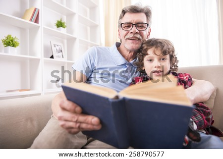 Grandfather and grandson are reading a book while sitting on the couch. - stock photo