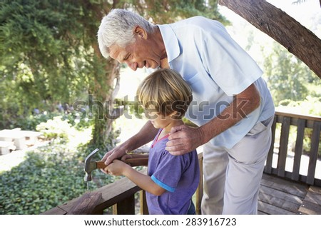 Grandfather And Grandson Building Tree House Together - stock photo