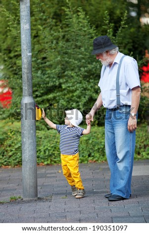 Grandfather and grandson crossing the street at the crosswalk - stock photo