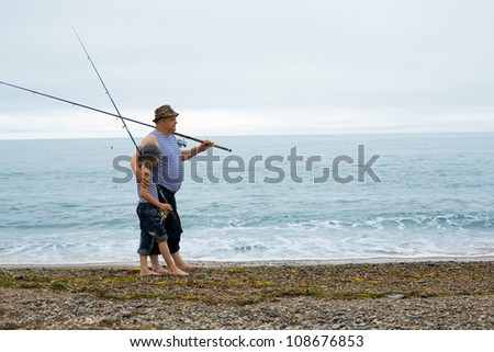 Grandfather and grandson fishing at the weekend at sea. - stock photo