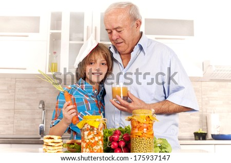 Grandfather and grandson in kitchen. - stock photo