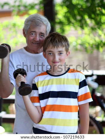 Grandfather and grandson of exercising with dumbbells - stock photo