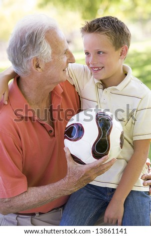 Grandfather and grandson outdoors with ball smiling - stock photo