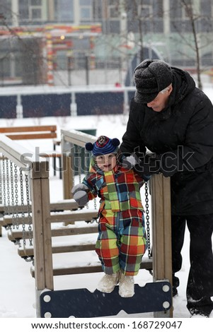 Grandfather and grandson playing at playground in winter - stock photo
