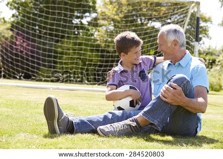 Grandfather And Grandson Playing Football In Garden - stock photo