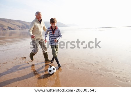 Grandfather And Grandson Playing Football On Winter Beach - stock photo