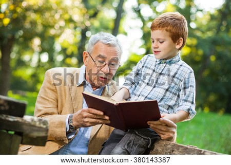 Grandfather and grandson reading book and learning about nature - stock photo