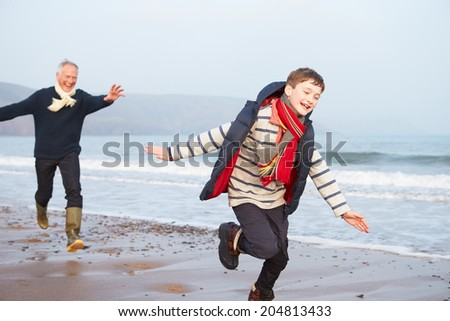 Grandfather And Grandson Running On Winter Beach - stock photo