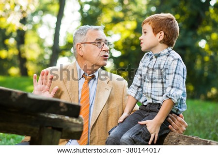 Grandfather and grandson sitting and talking in park - stock photo