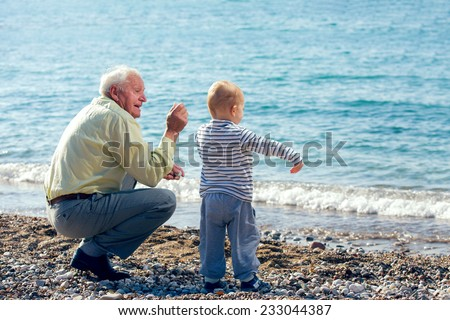 Grandfather and grandson throwing stones into the sea - stock photo