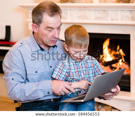 Grandfather and grandson using a laptop - stock photo