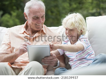 Grandfather and grandson using digital tablet on outdoor sofa - stock photo