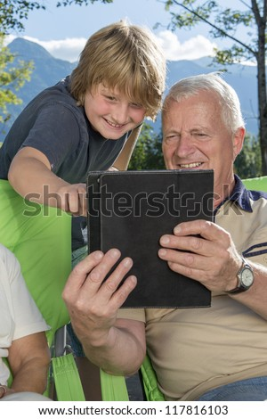 Grandfather and grandson using tablet computer outdoors - stock photo