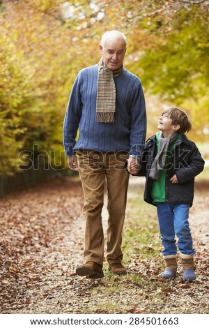 Grandfather And Grandson Walking Along Autumn Path - stock photo