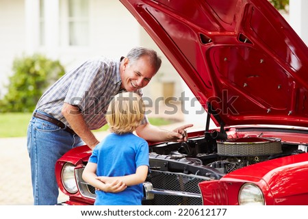 Grandfather And Grandson Working On Restored Classic Car - stock photo