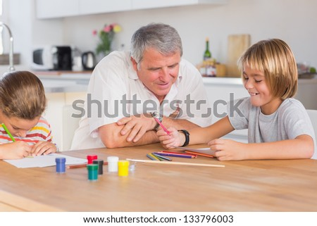 Grandfather and her grandchildren drawing in kitchen - stock photo