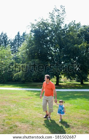 Grandfather and his granddaughter are walking in the park - stock photo