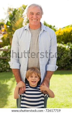 Grandfather and his grandson looking at the camera in the garden - stock photo
