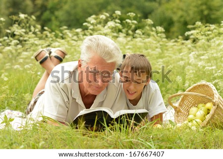 Grandfather and his grandson reading book outdoor - stock photo