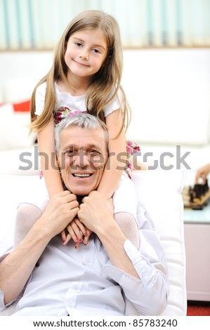 Grandfather and his little girl indoor - stock photo