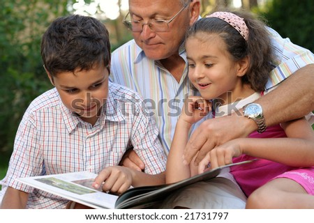 Grandfather and kids reading book outdoors - stock photo