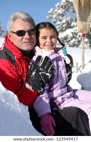 Grandfather and little girl in ski holidays - stock photo