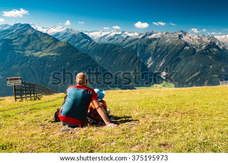 grandfather and young son observing paraglides flying over mountain peaks in austrian alps near kaprun - stock photo