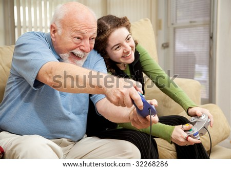 Grandfather enjoys playing video games with his teenage granddaughter. - stock photo