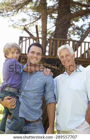 Grandfather, Father And Son Standing By Tree House Together - stock photo