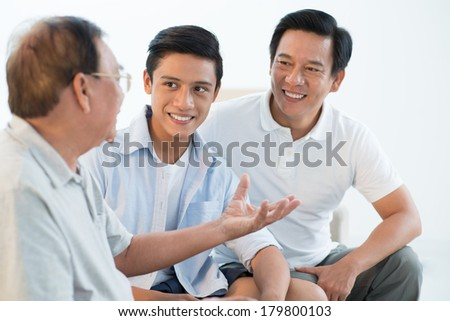Grandfather gesturing while telling interesting stories from his life on the foreground  - stock photo