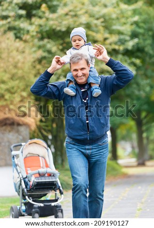 Grandfather Giving Grandson Ride On Back - stock photo