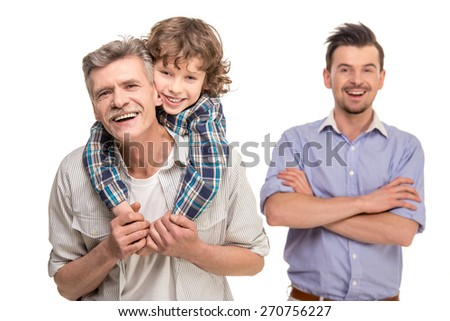 Grandfather giving piggyback ride to his son on background father. Isolated a white background. - stock photo