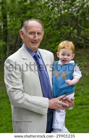 Grandfather holding grandson in garden - stock photo