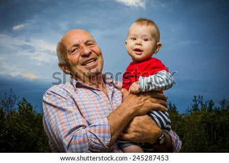 Grandfather holding grandson outdoors, against a sunset sky, smiling. - stock photo