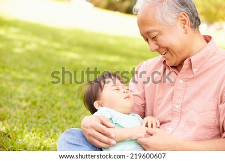 Grandfather Holding Sleeping Grandson In Park - stock photo