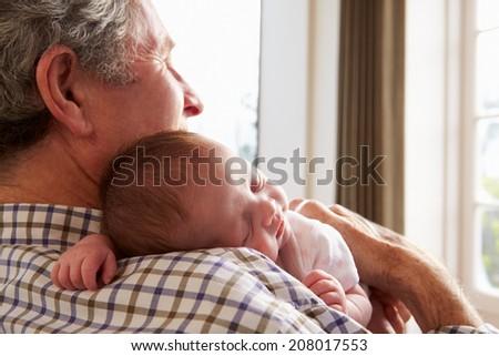 Grandfather Holding Sleeping Newborn Baby Granddaughter - stock photo