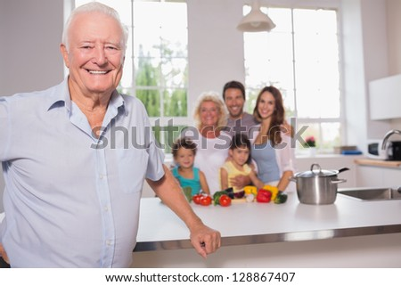 Grandfather in front of his family in the kitchen - stock photo