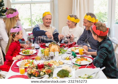 Grandfather in party hat carving chicken during dinner at home in the living room - stock photo