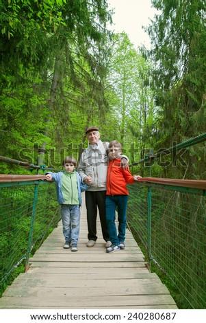 Grandfather of two grandchildren on a suspension bridge in the Park - stock photo