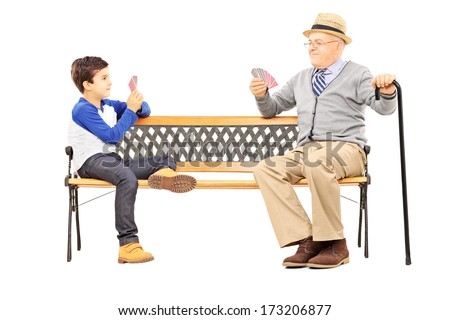 Grandfather playing cards with his nephew seated on bench isolated on white background - stock photo