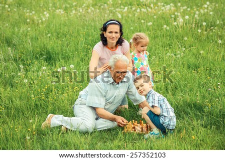 Grandfather playing chess with his daughter and granddaughter. family of three generations playing chess on a green meadow. - stock photo
