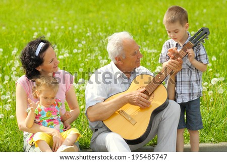 Grandfather playing guitar to his daughter and grandchildren outdoors. romantic portrait of three generations with the guitar. - stock photo