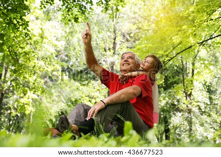 Grandfather pointing with finger his granddaughter something up in forest.  - stock photo