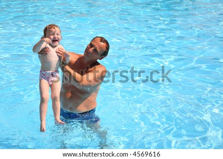 Grandfather standing in pool holds granddaughter - stock photo