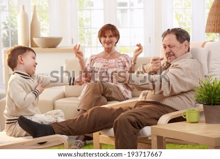 Grandfather telling story to grandson, happy grandmother watching in background, smiling. - stock photo