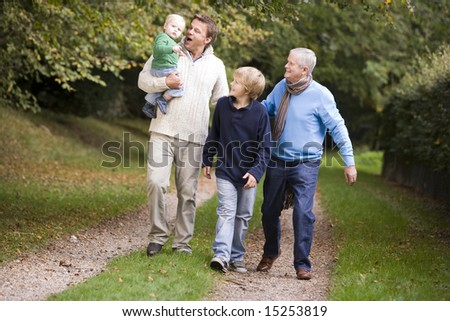 Grandfather walking with son and grandchildren along woodland path - stock photo