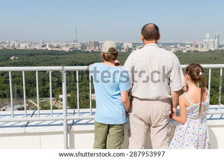 Grandfather with grandchildren admire the city view from the roof - stock photo