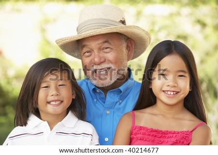 Grandfather With Grandchildren In Garden - stock photo