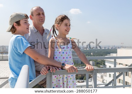 Grandfather with grandson and granddaughter admire the city view from the roof - stock photo